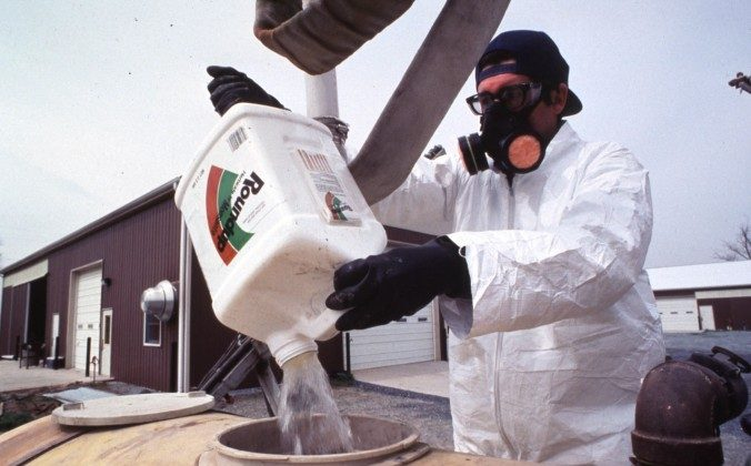 A farm worker handles Roundup, a common herbicide used in U.S. food production. A class action lawsuit accuses  Monsanto, the manufacturer of Roundup, of false advertising. (USDA)