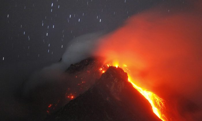 In this photo taken with slow shutter speed, hot lava flows from the crater of Mount Sinabung as seen from Tiga Serangkai, North Sumatra, Indonesia, early Monday, June 15, 2015.  (AP Photo/Binsar Bakkara)