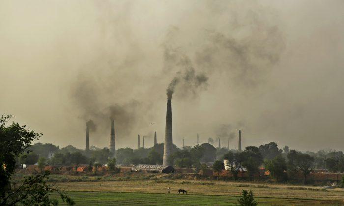 Smoke rises from chimneys of brick kilns on the outskirts of New Delhi, India, Tuesday, June 16, 2015. (AP Photo/Altaf Qadri)