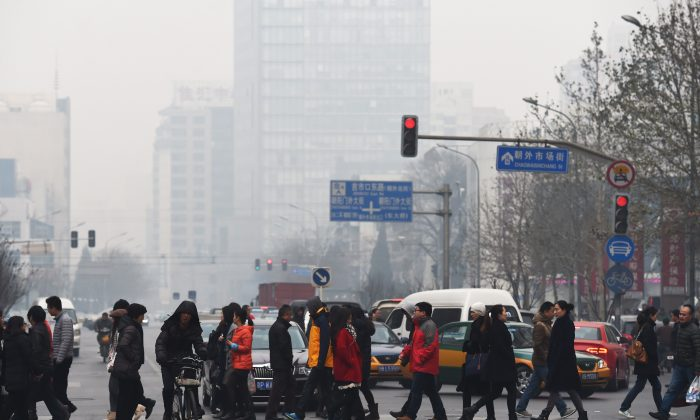Pedestrians cross a road on a polluted day in Beijing on December 9, 2014. (GREG BAKER/AFP/Getty Images)
