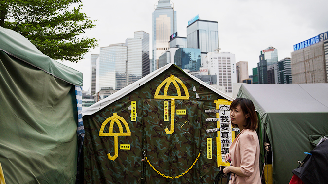 A woman stands in front of yellow umbrellas, a symbol of the pro-democracy movement, stuck on a tent outside the government headquarters in Hong Kong on June 13, 2015. (Dale de la Rey/AFP/Getty Images)