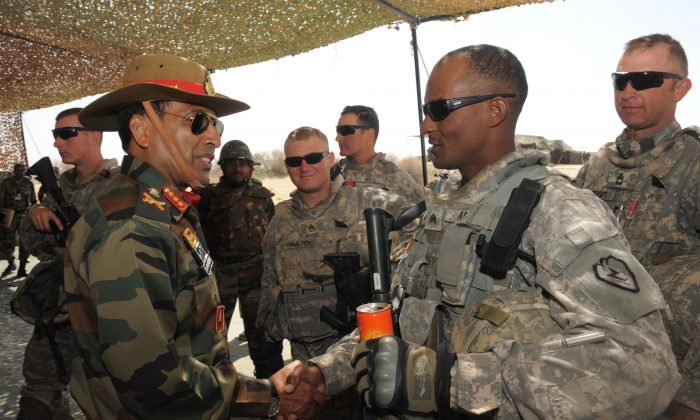 Indian army commander Lt. Gen. Gyan Bhushan (L) greets U.S. soldiers participating in a military exercise in Mahajan, India's northwestern state of Rajasthan, on March 13, 2012. (Sam Panthaky/AFP/Getty Images)
