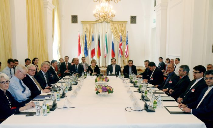 Delegates sit around a table prior to a bilateral meeting as part of the closed-door nuclear talks with Iran at a hotel in Vienna, Austria. Iran and six powers are still apart on all main elements of a nuclear deal with less than two weeks to go to their June 30 target date and will likely have to extend their negotiations, two diplomats tell The Associated Press. (AP/Ronald Zak)