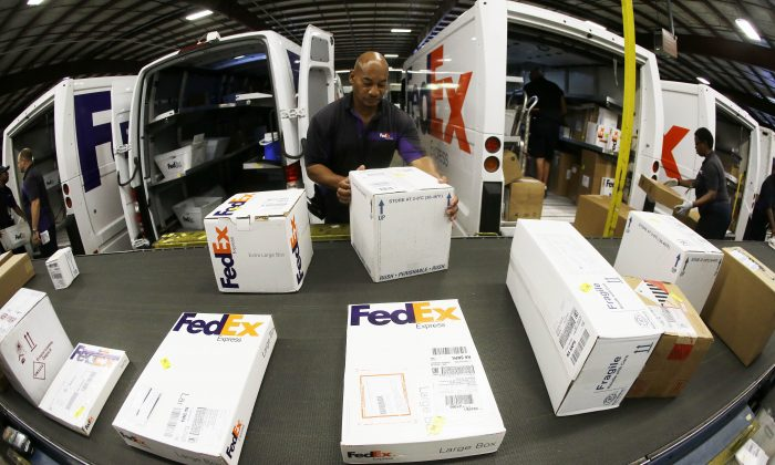 Workers load packages into delivery trucks at the FedEx Express station in Nashville, Tenn. (AP Photo/Mark Humphrey)
