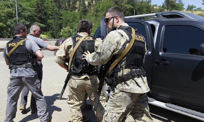 Georgian police commandos get into a car after a tiger that broke loose after flooding at a Zoo, was shot by police in Tbilisi, Georgia, Wednesday, June 17, 2015. (AP Photo/Shakh Aivazov)