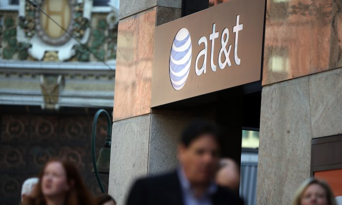 People pass an AT&T store in San Francisco on Oct. 23, 2013. (Justin Sullivan/Getty Images)