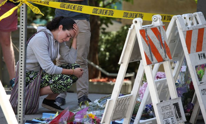A woman cries as she leaves flowers at the scene of the balcony that collapsed at an apartment building near UC Berkeley in Berkeley, Calif., on Tuesday  June 16, 2015. (Justin Sullivan/Getty Images)