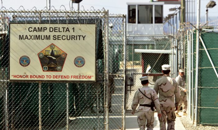 U.S. military guards walk within Camp Delta military-run prison, at the Guantanamo Bay U.S. Naval Base, Cuba, on June 2, 2006. (AP Photo/Brennan Linsley)