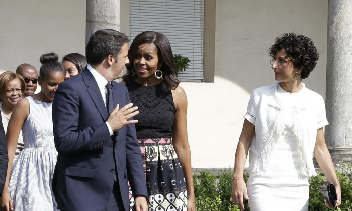"U.S. first lady Michelle Obama talks with Italian premier Matteo Renzi as she arrives at the Santa Maria delle Grazie church to see Leonardo's masterpiece ""The Last Supper"", after participating in a cooking demonstration at the James Beard American Restaurant with Italian and American middle school students in Milan, Italy, Wednesday, June 17, 2015.  At right is Renzi's wife Agnes, while behind are Michelle's daughters Malia and Sasha and her mother Marian Robinson. Michelle Obama is in Milan on the second leg of a European trip that puts an international spin on her core initiatives. (AP/Antonio Calanni)"