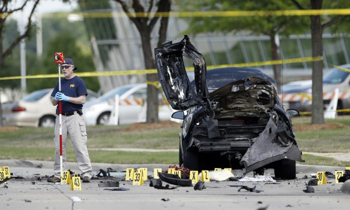 FILE - In this May 4, 2015 file photo, FBI crime scene investigators document evidence outside the Curtis Culwell Center in Garland, Texas. (AP Photo/Brandon Wade, File)