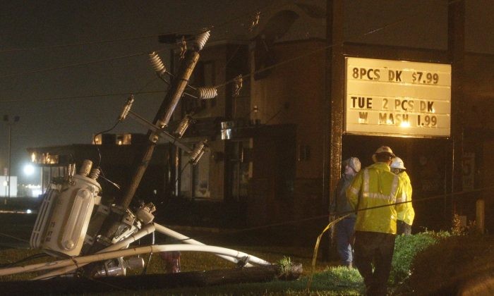Center Point crews work to restore power after a power line fell on Highway 60 due to high winds from Tropical Storm Bill on Tuesday, June 16, 2015, in Wharton, Texas. (AP/Patric Schneider)