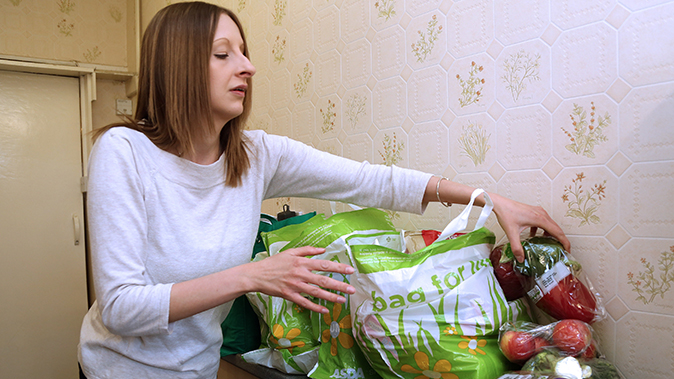 A woman unloads grocery at her home on March 23, 2015. (Geoff Caddick/AFP/Getty Images)