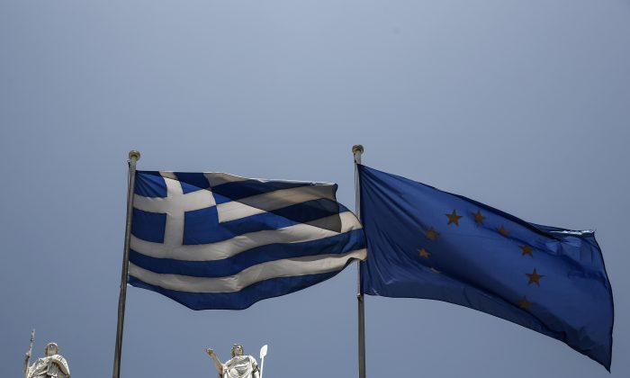 A Greek and a European Union flags flutter in front of statues of goddess Athena, left, and Nautilia, in front of Benaki museum in Athens, Greece, on Wednesday, June 17, 2015.  (AP Photo/Yorgos Karahalis)