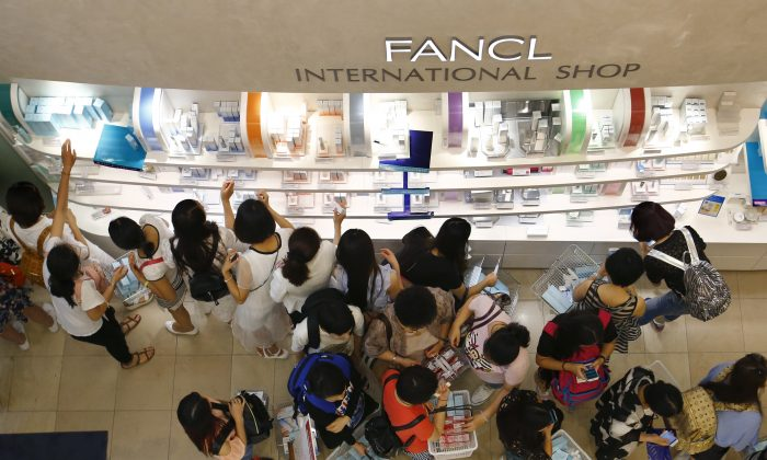 In this Wednesday, June 17, 2015 photo, Chinese tourists choose goods at a cosmetics store in Tokyo's Ginza shopping district.  (AP Photo/Shizuo Kambayashi)