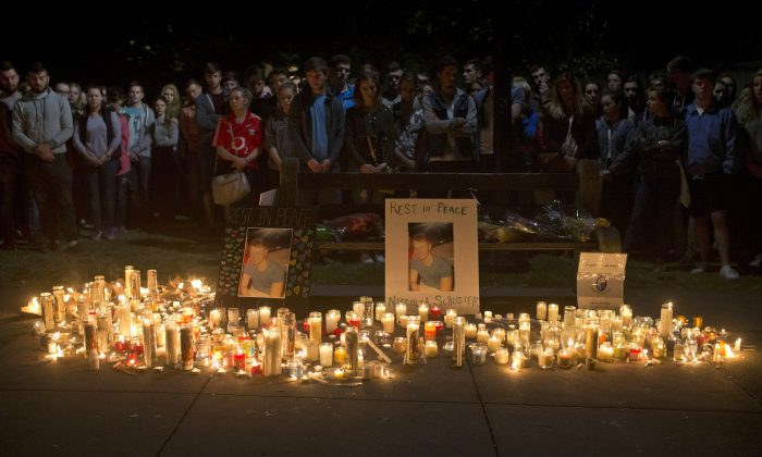 Mourners stand by during a candlelight vigil for six Irish students Wednesday, June 17, 2015, in Berkeley, Calif.  (AP Photo/Beck Diefenbach)