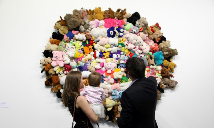 A mother, father, and their daughter look at a piece of art made of stuffed animals in Basel, Switzerland, on June 17. (Michele Tantussi/Getty Images)