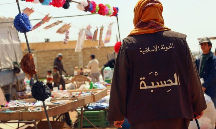 "In this photo released on April 17, 2015 by a militant website, which has been verified and is consistent with other AP reporting, a member of the Islamic State group's vice police known as ""Hisba,"" patrols a market in Raqqa City, Syria. The Arabic words on the vest read, ""The Islamic State - Hisba (vice police)."" (Militant website via AP)"