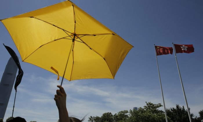 A pro-democracy protester raises a yellow umbrella in front of a Chinese national flag and a Hong Kong flag after lawmakers voted against the election reform proposals in Hong Kong, June 18, 2015. (AP Photo/Vincent Yu)