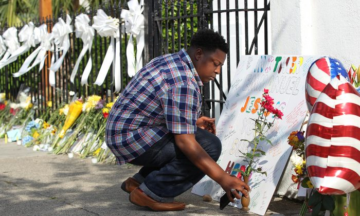 Jermaine Jenkins, 25, Johns Island, S.C., sets out a sign and some flowers in front of the Emanuel AME Church on Friday, June 19, 2015 in Charleston, S.C.