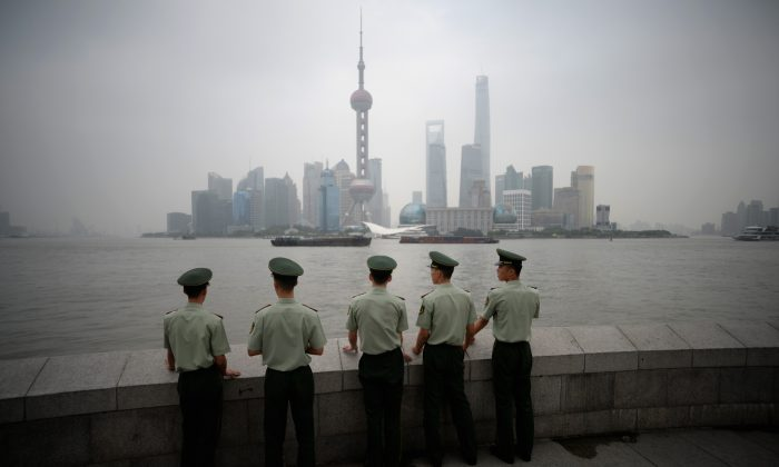 Paramilitary policemen stand in front of the skyline of the Lujiazui Financial District in Pudong in smog in Shanghai. (Johannes Eisele/AFP/Getty Images)