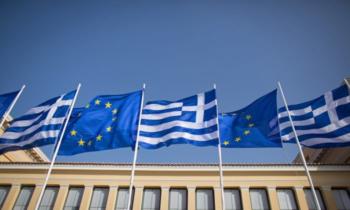 The national flag of Greece and the flag of the European Union fly above a government building ahead of the general election on Sunday on January 23, 2015 in Athens, Greece. (Matt Cardy/Getty Images)