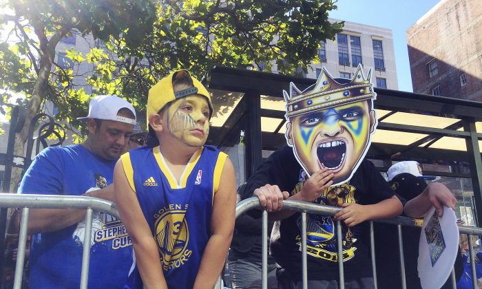 Golden State Warriors fans Vic Fontana, far left, and his son Rocco, second from left, wait along the route for the NBA basketball team's world championship parade in Oakland, Calif.