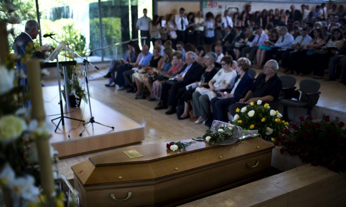 Flowers  lay on top of a coffin with the remains of Robert Oliver Calvo, a business man who was on board of the Germanwings jet which crashed in the French Alps, during a religious funeral service, in Montcada, near Barcelona, Spain, Saturday, June 20, 2015. Three months after the Germanwings jet crashed in the French Alps, hundreds of tearful mourners have packed a funeral home to say goodbye to Robert Oliver Calvo — a passenger who died while on a business trip. (AP Photo/Emilio Morenatti)