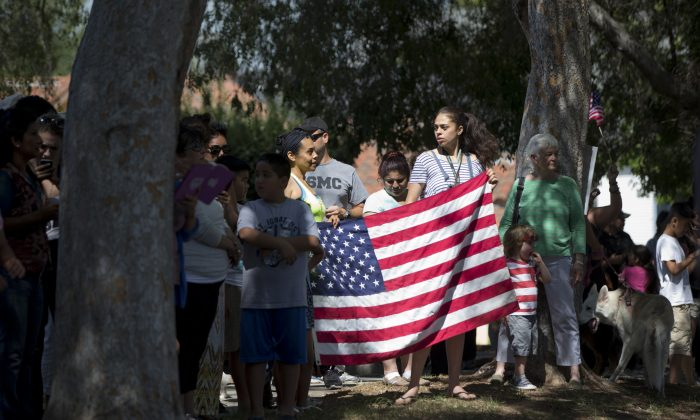 Residents stand along the President Barack Obama's motorcade route, Friday, June 19, 2015, in the Highland Park neighborhood of Los Anageles, Calif., hoping to see the president as he drives past en route to an interview with comedian Marc Maron near by. (AP Photo/Carolyn Kaster)