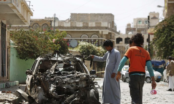 Boys stand near a wreckage of a car at the site of a car bomb attack in Sanaa, Yemen, Thursday, June 18, 2015. A series of Islamic State-claimed bombings in Yemen's rebel-controlled capital killed several people and wounded dozens Wednesday night amid the country's raging war. (AP Photo/Hani Mohammed)