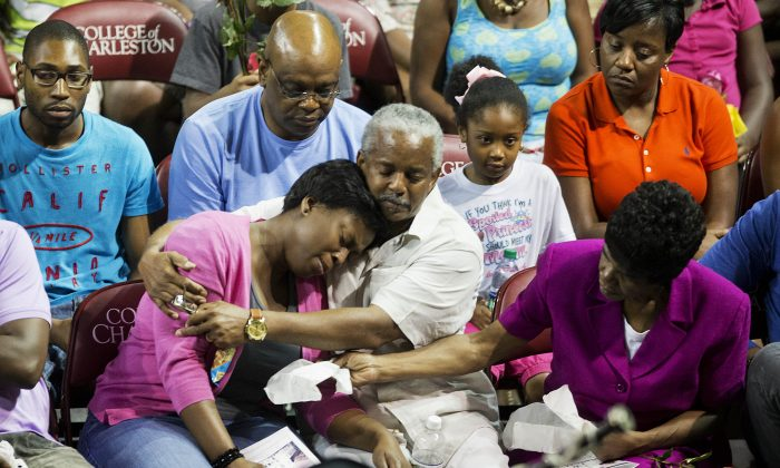 Family members of the victims of a shooting at Emanuel AME Church comfort one another during a memorial service, Friday, June 19, 2015, in Charleston, S.C. (AP Photo/David Goldman)