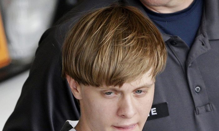 Charleston, S.C., shooting suspect Dylann Storm Roof is escorted from the Cleveland County Courthouse in Shelby, N.C., on June 18, 2015.  (AP Photo/Chuck Burton)