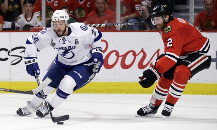 Tampa Bay Lightning's Ryan Callahan, left, handles the puck as Chicago Blackhawks' Duncan Keith watches during the first period in Game 6 of the NHL hockey Stanley Cup Final series on Monday, June 15, 2015, in Chicago. (AP Photo/Nam Y. Huh)