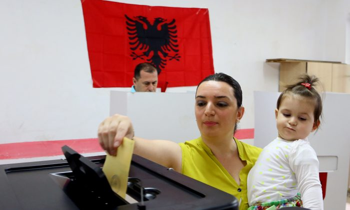An Albanian casts her ballot for the local municipal elections, a key step in the country's efforts to launch membership negotiations with the European Union, in Tirana, Sunday, June 21, 2015. Some 3.4 million eligible voters cast their ballots in the country's seventh local polls since the fall of communism in 1990 to elect 61 mayors and 1,595 municipal counsellors. (AP Photo/Hektor Pustina)