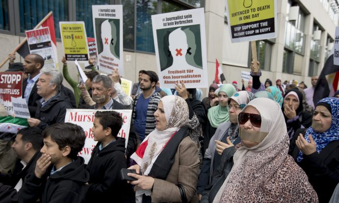 "People attend a protest rally in front of a court to support the release of the journalist Ahmed Mansour in Berlin, Germany, Sunday, June 21, 2015. Ahmed Mansour, 52, a senior journalist with the Qatar-based broadcaster Al-Jazeera, was detained at Tegel airport on Saturday on an Egyptian arrest warrant, Al-Jazeera said. Poster at center reads: ""To be a journalist is no crime. Freedom for the journalist Ahmed Mansour"". (AP Photo/Michael Sohn)"