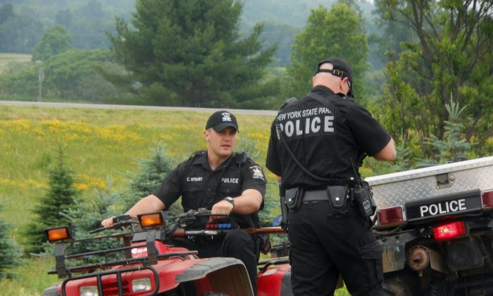 Authorities speak to one another during a search for two prisoners that escaped Clinton Correctional Facility two weeks prior, Saturday, June 20, 2015, in Allegany County, N.Y. (Kathryn Ross/The Wellsville Reporter via AP)
