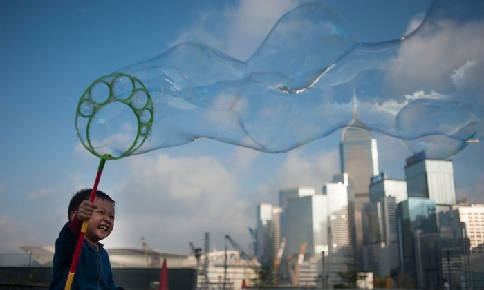 In this file photo, a boy waves a wand of bubbles up in the air in Hong Kong. (Anthony Kwan/Getty Images)