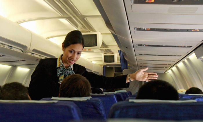 A Garuda Indonesia flight attendant helps a passenger during a flight from Padang to Jakarta in this file photo. (Adek BerryAFP/Getty Images)