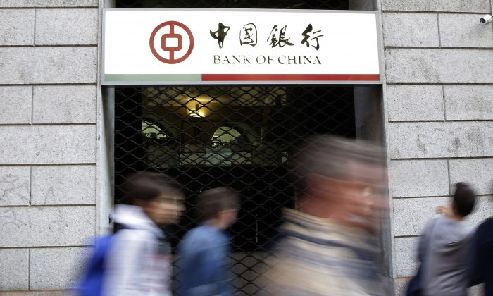 Residents walk past the Bank of China branch in downtown Milan, Italy, on April 15. Italian prosecutors are seeking to indict over 200 people and the Bank of China in connection with a massive money-laundering investigation. (AP Photo/Antonio Calanni, File)