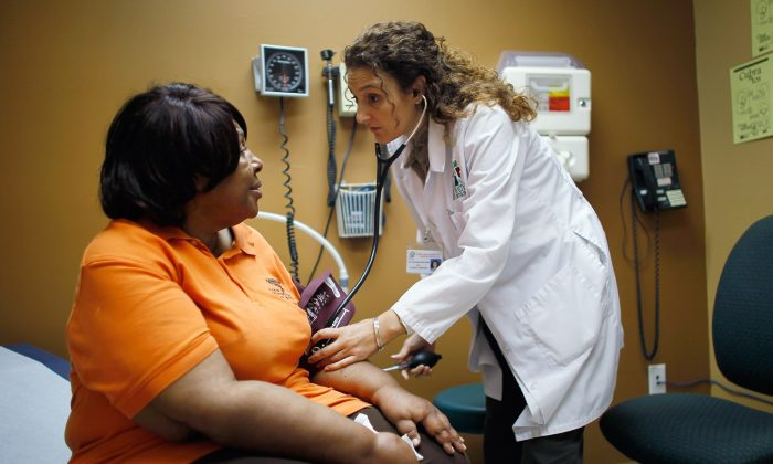 Brenda Major (L), who said she had a pre-existing condition that made it impossible to find insurance that would cover her until the Affordable Care Act, is examined by Dr. Fernanda Mercade during a routine checkup at the Jessie Trice Center for Community Health clinic. (Photo by Joe Raedle/Getty Images)
