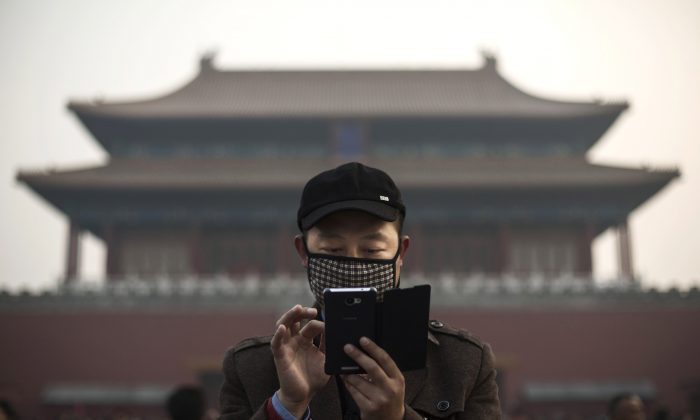 A Chinese man uses his smartphone outside the Forbidden City in Beijing on Nov. 20, 2014. (Kevin Frayer/Getty Images)
