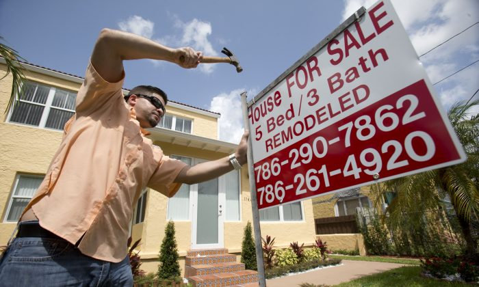 Robert Almirall, director of marketing and special assets coordinator for Mederos & Associates Real Estate Inc., puts up a sign in front of a home in the Shenandoah neighborhood of Miami.