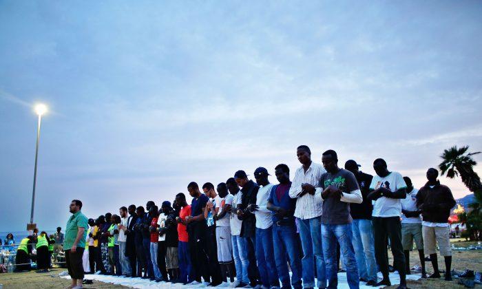 Migrants pray at the Franco-Italian border in Ventimiglia, Italy, Sunday, June 21, 2015. (AP Photo/Thibault Camus)