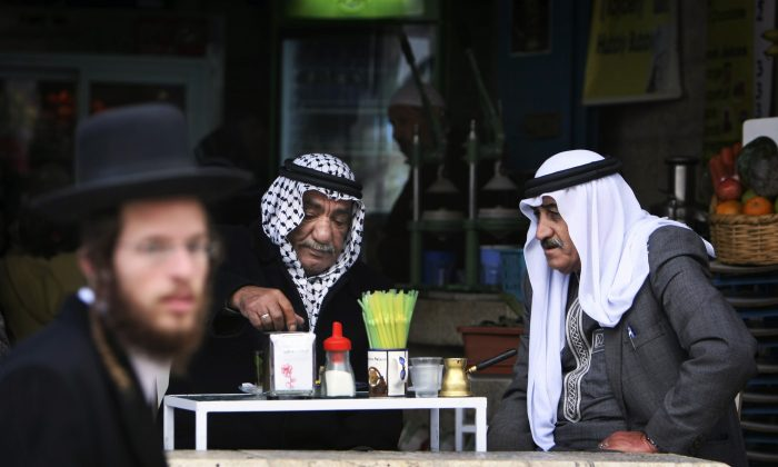 In this Dec. 8, 2009 photo, an ultra-orthodox Jewish man passes by Palestinians sitting in a coffee shop near Damascus gate in Jerusalem's Old City. (AP Photo/Tara Todras-Whitehill)