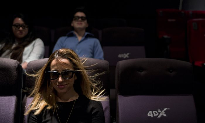 A wind effect is demonstrated on marketing director Yassamine Wahab at the CJ's 4DX Lab in the Hollywood Section of Los Angeles. (AP Photo/Jae C. Hong)