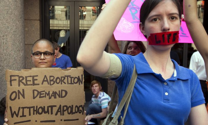 In a Tuesday July 2, 2013 photo, pro-abortion rights supporter Yatzel Sabat, left, and anti-abortion protestor Amanda Reed demonstrate at the state Capitol in Austin, Texas. (Jay Janner/Austin American-Statesman via AP)