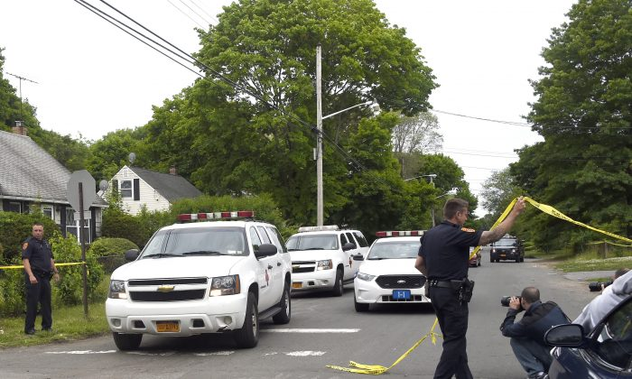 Vans carrying the bodies of victims exits the scene on Davidson Street in Wyandanch, N.Y., where three people where found shot to death inside a car and a fourth person was injured on Thursday, June 4, 2015. (AP Photo/Kathy Kmonicek)
