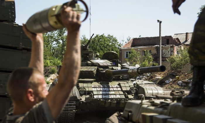 A Russia-backed rebel loads shells into a tank at Donetsk airport, eastern Ukraine, on June 12, 2015. (Mstyslav Chernov/AP Photo)