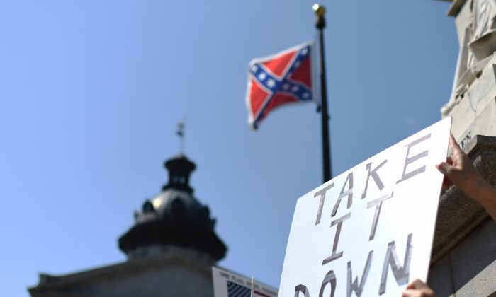 Protesters hold a sign during a rally to take down the Confederate flag at the South Carolina Statehouse, Tuesday, June 23, 2015, in Columbia, S.C. (AP Photo/Rainier Ehrhardt)