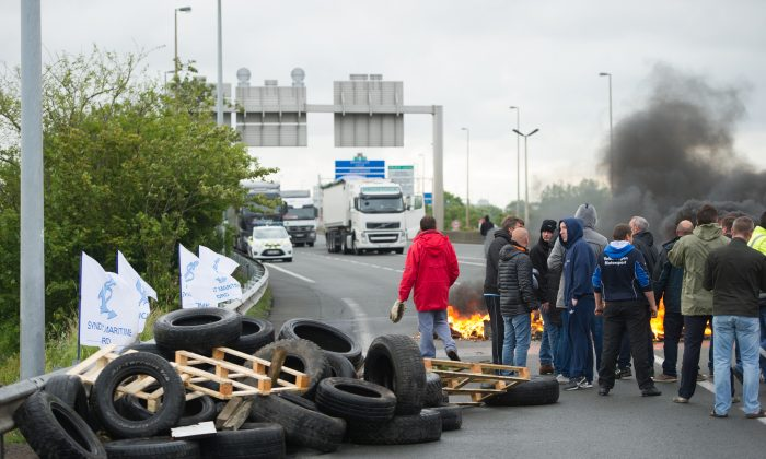 Striking ferry workers burn tyres as they block a ramp leading into the Eurotunnel before being dispersed by riot police in Calais, northern France, Tuesday, June 23, 2015. A strike by workers in the northern French port of Calais has left all passenger ferry service between the city and the English city of Dover suspended and briefly slowed traffic in the Eurotunnel. (AP)