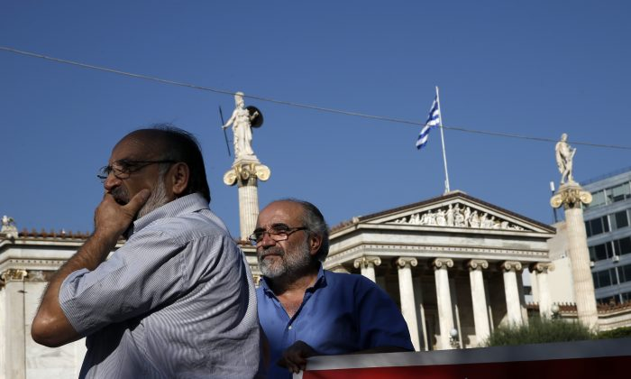Elderly men take part in an anti-austerity protest organized by pensioners' unions in Athens on Tuesday, June 23, 2015. (AP Photo/Petros Giannakouris)